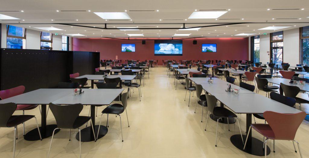 Kantine als Veranstaltungsraum mit großen Screens, Mikrofonen und Beschallung